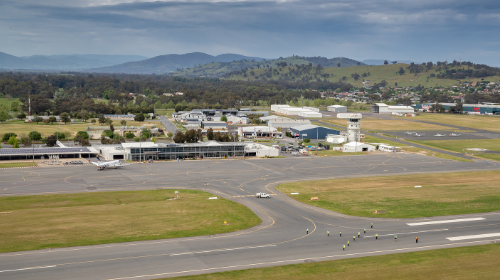 Aerial picture of airport team on tarmac with reporting officer ute, plane and terminal in background